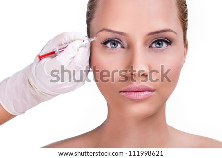 Beautiful woman gets botox injection in her face, correction upper lids - stock photo