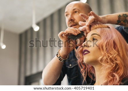 Beautiful woman getting haircut by hairdresser in the beauty salon. - stock photo