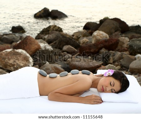 Beautiful woman getting hot stones treatment out in the nature. - stock photo