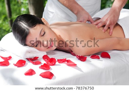 Beautiful woman getting massage and spa treatment in natural setting - stock photo