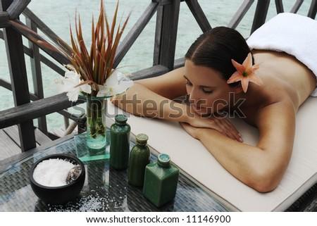 beautiful woman getting spa treatment at daylight near the ocean - stock photo