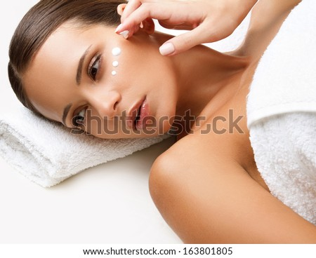 Beautiful Woman Getting Spa Treatment. Cosmetic Cream on a Cheek. Skin Care