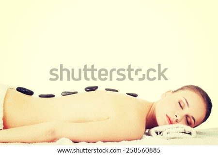 Beautiful woman getting stone massage at spa. - stock photo