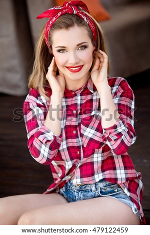 Beautiful woman. Girl in jeans, plaid shirt and bandana outdoors, pin-up