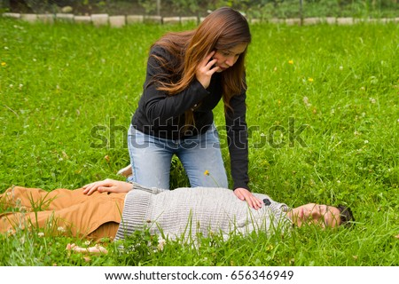 Beautiful woman giving first aid to a handsome young man and using her cellphone to call the ambulance, cardiopulmonary resuscitation, in a grass background