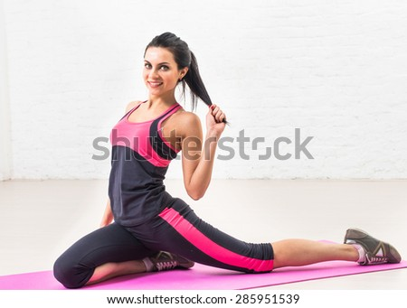 Beautiful woman goes in for sports, fitness, doing exercises with a smile, stretched, kneaded. Healthy lifestyle, health. - stock photo