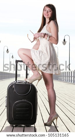 Beautiful woman going on a sea mooring suitcase pier - stock photo