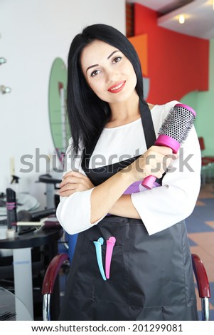 Beautiful woman hairdresser in beauty salon - stock photo