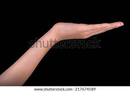 Beautiful woman hand holding isolated on black background - stock photo