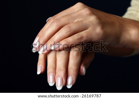 Beautiful woman hand with french manicure, isolated on black background