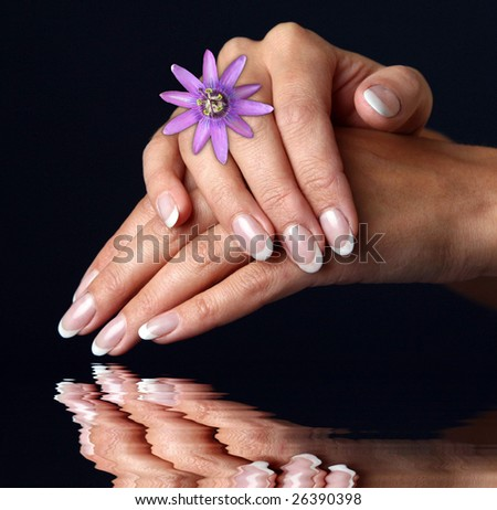 Beautiful woman hand with french manicure, over black background - stock photo