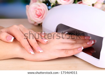 Beautiful woman hands and lamp for nails on table close up - stock photo