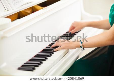 beautiful woman hands playing music on white grand piano - stock photo