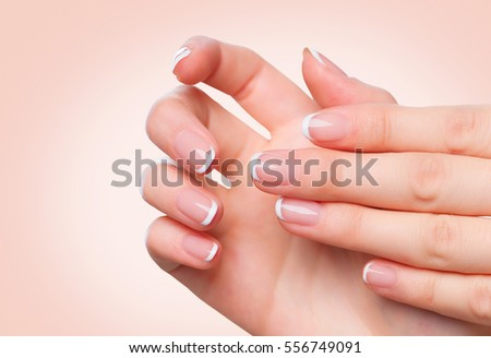 Beautiful Woman Hands. Spa and Manicure concept. Female hands with french manicure. Soft skin, skincare concept. Beauty nails. over beige background