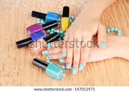 Beautiful woman hands with blue manicure holding beads and bottles with nail polish, on color background - stock photo