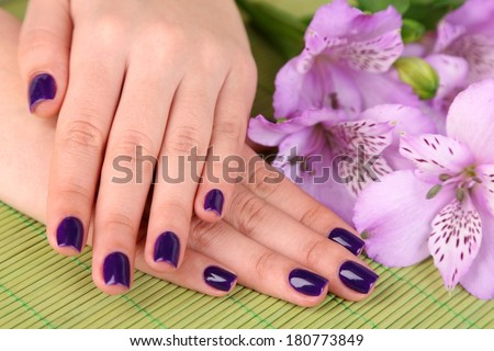 Beautiful woman hands with flowers on bamboo background