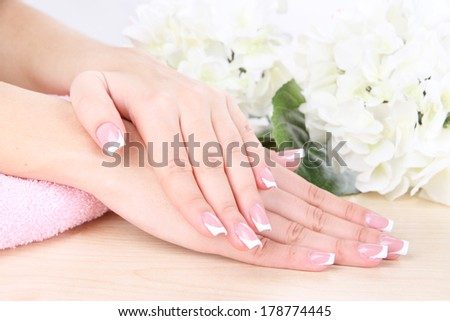 Beautiful woman hands with french manicure and flowers on table close up - stock photo
