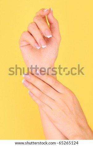 Beautiful woman hands with french manicure on yellow background - stock photo
