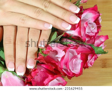 Beautiful woman hands with French manicure rose background