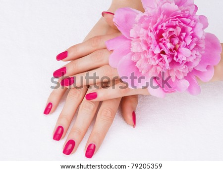 Beautiful woman hands with manicure lying down on white towel with a pink flower - stock photo