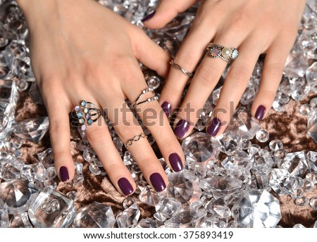Beautiful woman hands with purple pattern polish nails and silver stacking rings and bracelets on a ice diamonds background - stock photo