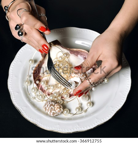 Beautiful woman hands with red pattern polish manicured nails and silver stacking rings and bracelets eating abstract food pearl and shells on a ice diamonds background - stock photo