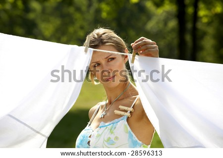 Beautiful woman hanging clothes on the line outdoors - stock photo