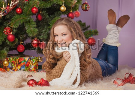 Beautiful woman hanging toy on Christmas tree