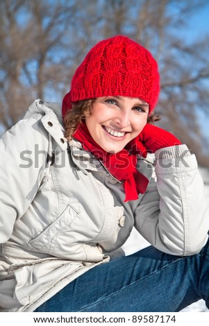 Beautiful woman has a snowball on a red cap, winter concepts - stock photo