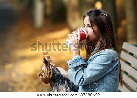 Beautiful woman have lunch while strolling with her dog in the park - stock photo