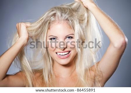 Beautiful woman having a bad hair day - stock photo