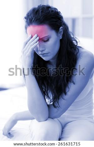 Beautiful woman having a headache sitting in bed - stock photo