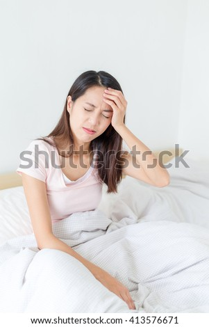 Beautiful woman having a headache sitting in bed