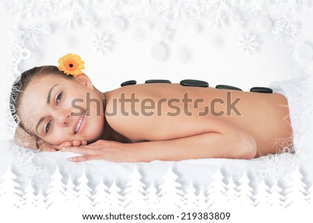 Beautiful woman having a hot stone massage while looking at the camera against fir tree forest and snowflakes - stock photo
