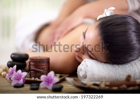 Beautiful woman having a wellness back massage at spa salon - stock photo