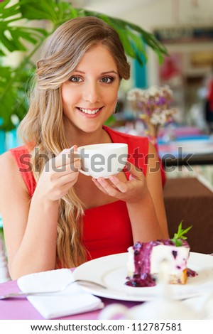 beautiful woman having breakfast at cafe - stock photo