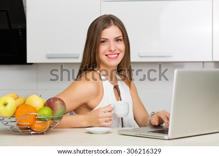 Beautiful woman having coffee and fruits for breakfast
