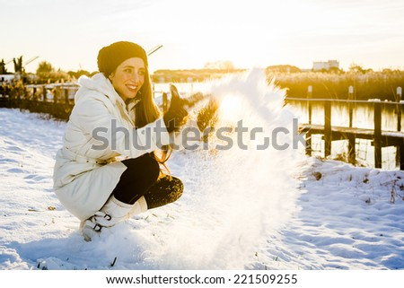 Beautiful woman having fun with snow during a cold winter day. - stock photo