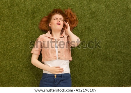 Beautiful woman having headache while lying on green grass in park. Pretty lady with red hair touching her stomach. - stock photo