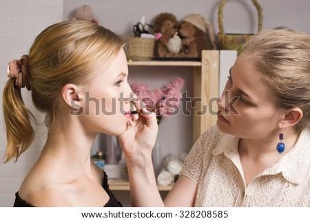 Beautiful woman having lipstick applied by make-up artist - stock photo