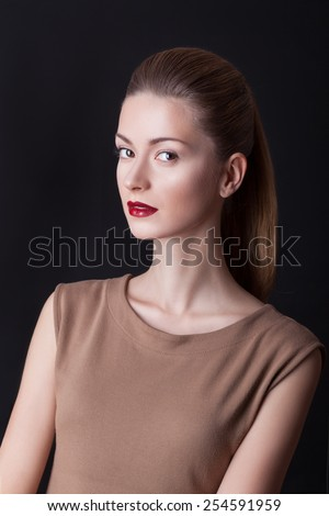 BEAUTIFUL WOMAN HEAD, perfect skin and makeup on her face. Portrait of an attractive woman on a black background,cream dress.