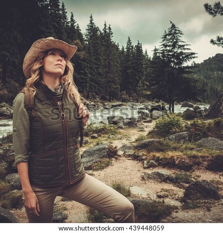 Beautiful woman hiker enjoying amazing landscapes near wild mountain river. - stock photo