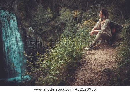 Beautiful woman hiker sitting near waterfall in deep forest. - stock photo