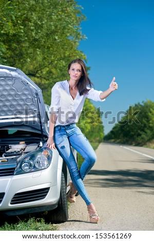 Beautiful woman hitchhiking by a broken car - stock photo