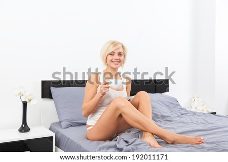 beautiful woman hold cup of coffee lying on bed, bedroom home, young blond girl happy smile morning - stock photo