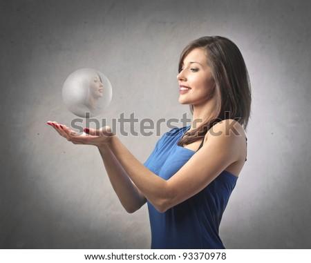 Beautiful woman holding a crystal ball - stock photo