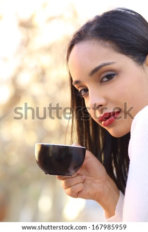 Beautiful woman holding a cup of coffee outdoor with an unfocused background            - stock photo