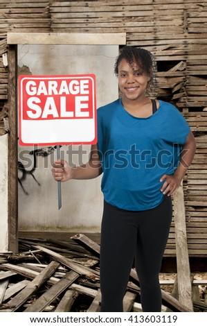 Beautiful woman holding a garage sale sign - stock photo