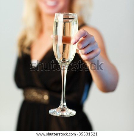 Beautiful woman holding a glass of champagne and smiling at the camera with focus on champagne - stock photo