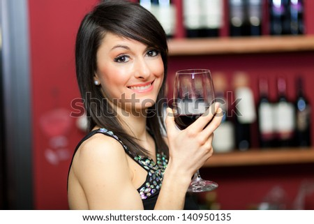 Beautiful woman holding a glass of wine  - stock photo